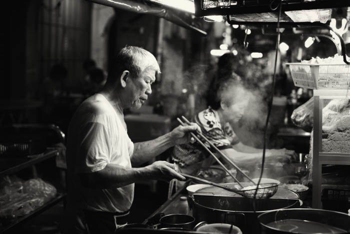 Night street shot of a man cooking in a food stall
