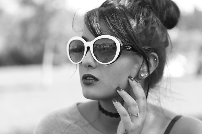 Black and white product photography headshot of a model with a reflection in white-framed sunglasses