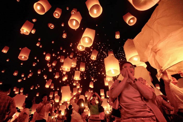 Hundreds of floating candles drift into the dark sky - travel photography