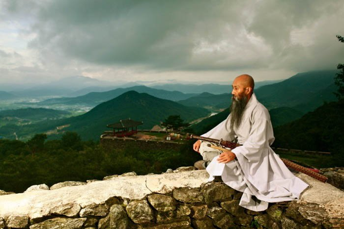 an image of a monk with hills in the background - travel photography