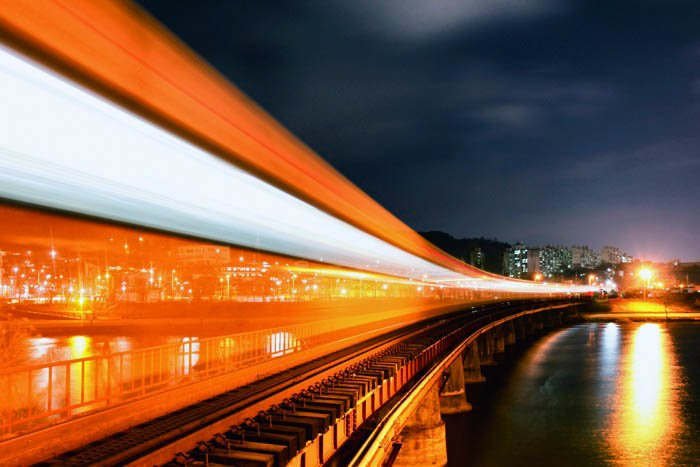A long exposure of a train passing infront of a city