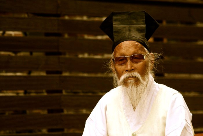 Portrait of a man wearing traditional Korean clothes and sunglasses, wooden fence in the background.