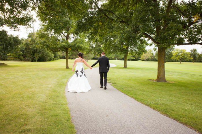 A bride and groom posing outdoors walking away from the camera