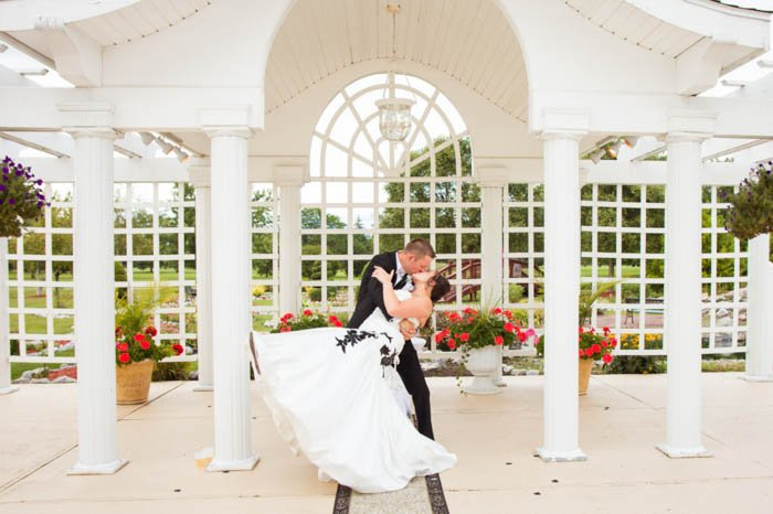Wedding portrait of the couple posing outdoors with the dip kiss