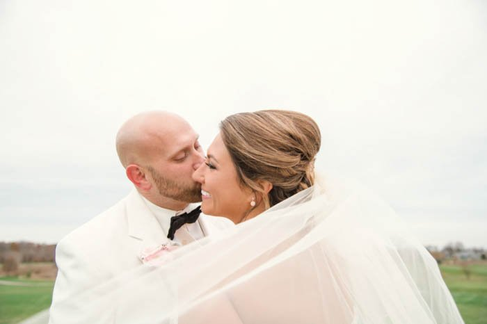 Wedding portrait of the couple posing outdoors with the veil