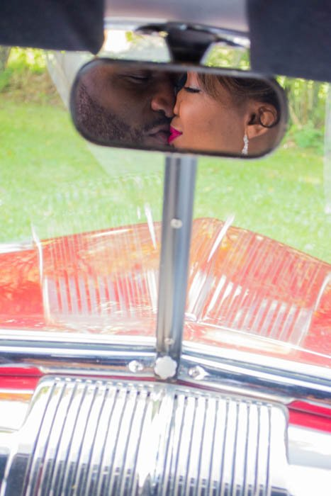 Car mirror reflection of a newlywed couple kissing