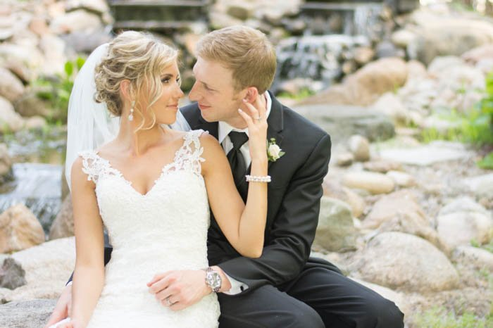 A bride and groom posing outdoors seated down