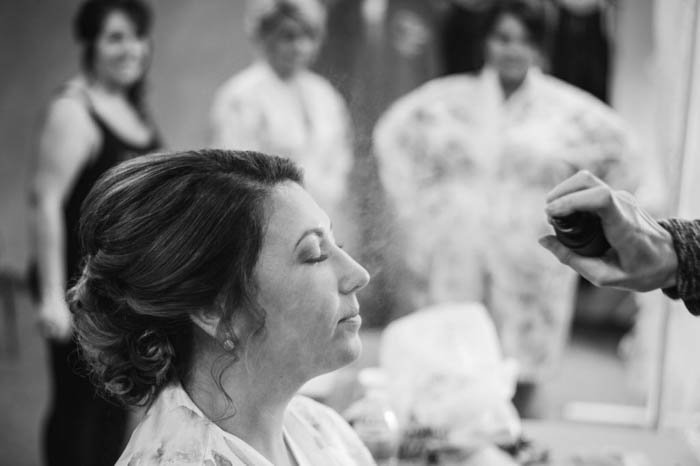 black and white wedding photo of bride getting her makeup done with bridesmaids in the background