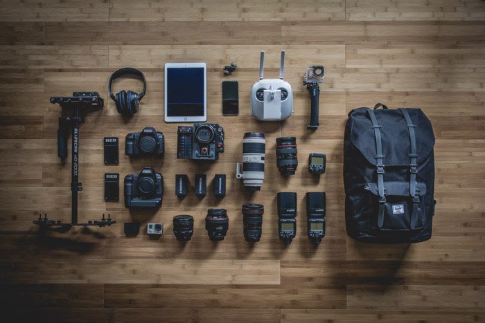 a flay lay of a camera bag and its equipment spread on a wooden table