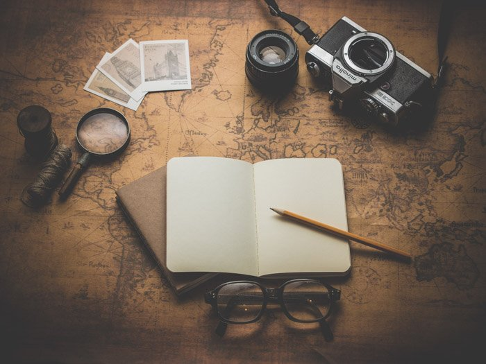 a flay lay of a camera, journals, glasses, and items against a world map