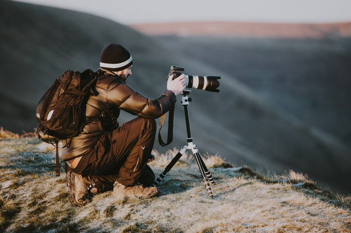 an image of a man in the mountains setting a camera with telephoto lens on a tripod