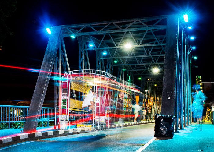 Light tails of a tram on a bridge at night