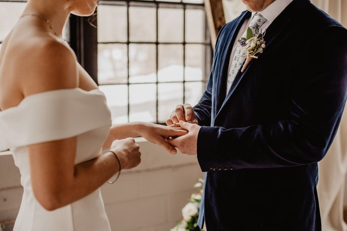 Close up of the bride and Groom holding hands during a wedding ceremony