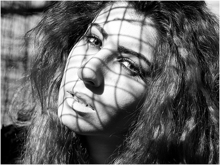 A greyscale portrait of a female model with dappled lighting on her face