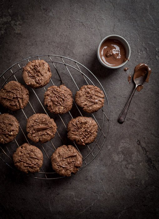 Flat lay of cookies cooling on a wire beside a bowl of chocolate