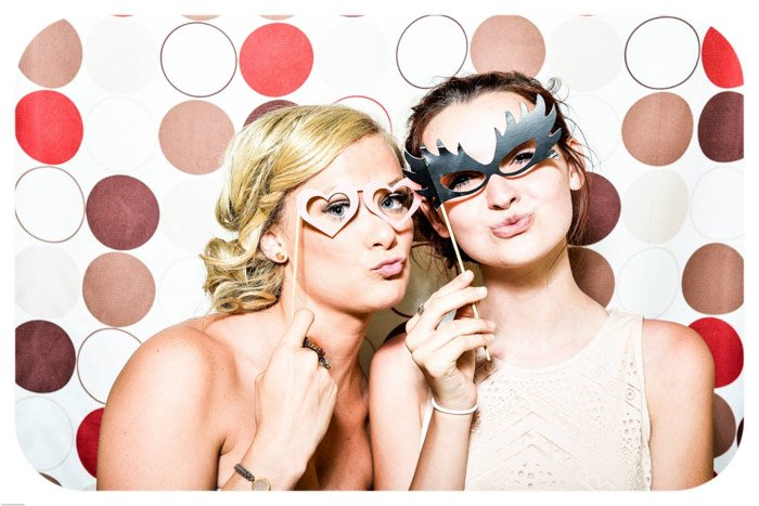 two young girls posing with masks in front of a colourful photo background