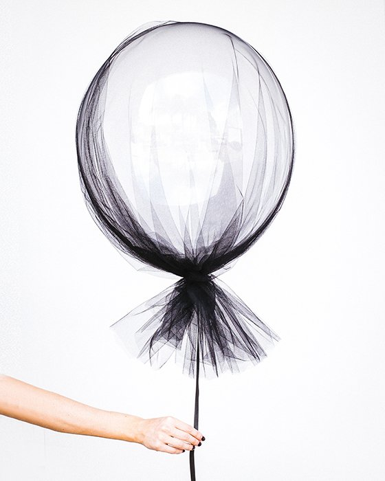 A person holding a lace balloon