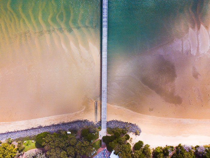 straight down drone photography of a long wooden bridge in shallow water capturing symmetry by combining natural and man-made features