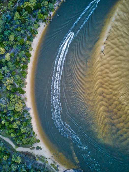 drone photography capturing the contrasting textures of a forest, coast, water and sand