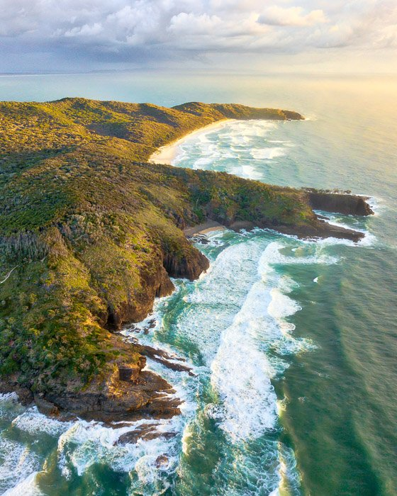 side-lighting drone photography of a rugged coastline and seascape on a bright cloudy day