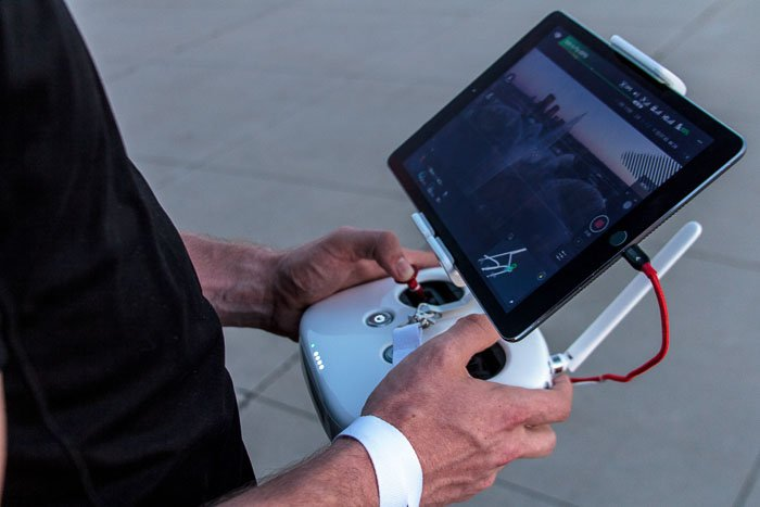 image of a man using a tablet for controlling drone landscape photography