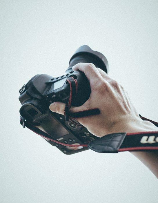 A person holding a Canon DSLR