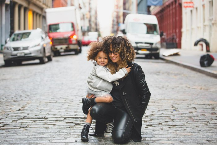 Casual family photography of a mother and daughter hugging on a street