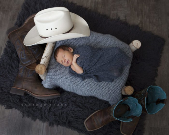 A newborn sleeping surrounded by props