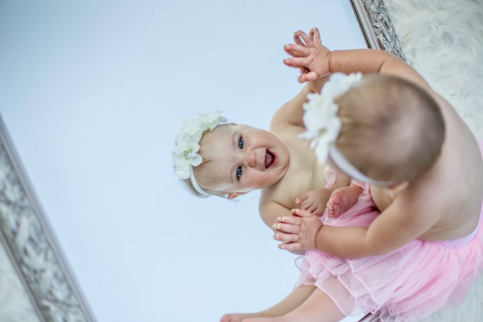 A cute newborn portrait of a baby looking in the mirror