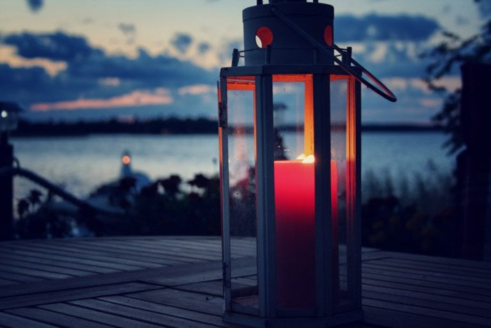 Red candle lit inside a lantern set on a wooden table next to a lake at dusk