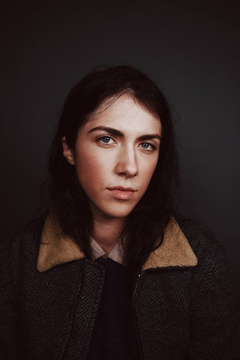 Serious female model looking into the camera, standing in front of a black background, wearing a sheep skin lined jacket