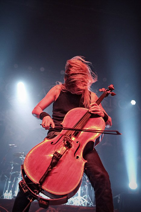 A girl playing an electric cello onstage