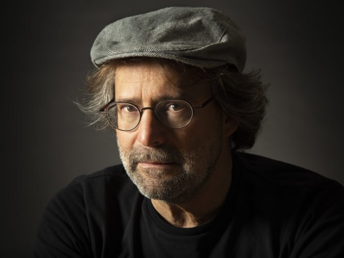 A studio portrait of a man in hat and glasses