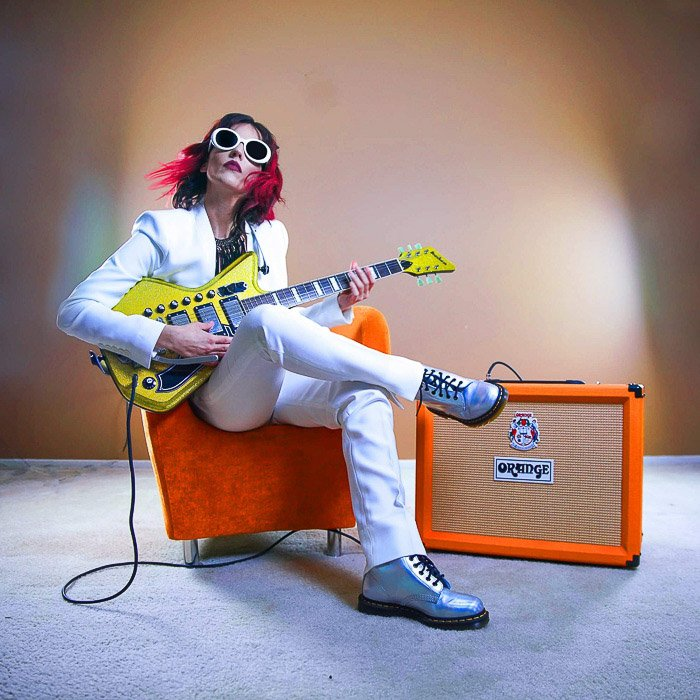 A girl playing electric guitar with orange amp