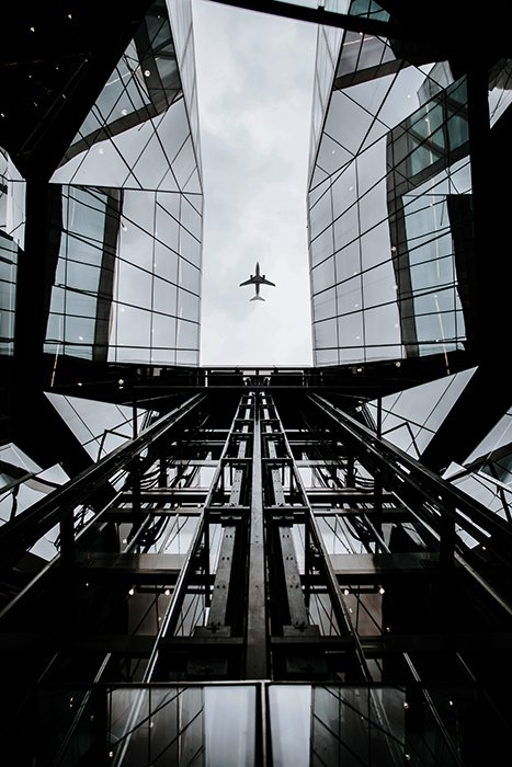 Birds eye view of an airplane flying over a glass roofed building