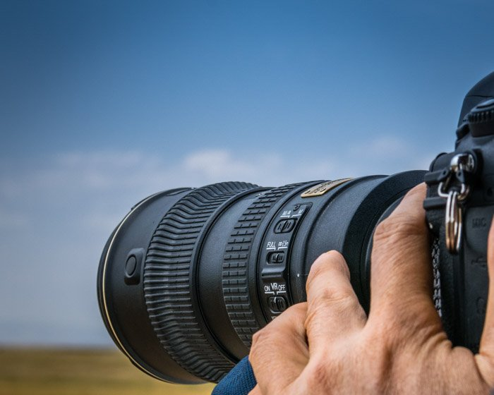 A photographer using a telephoto lens for stunning wildlife photography shots