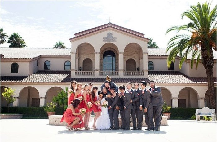 The wedding party poses outside a house. Amateur wedding photography