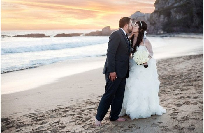 a married couple posing and kissing on a beach in sunset