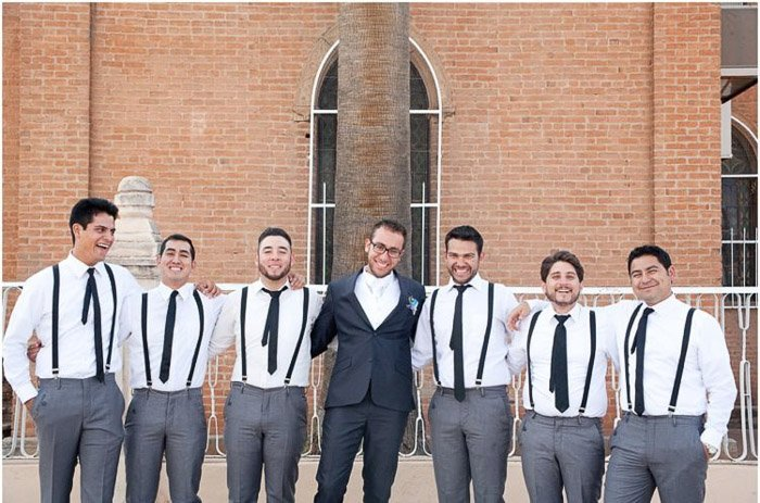 Wedding party photo of the groom in the middle of 6 groomsmen outside a church. Amateur wedding photography.