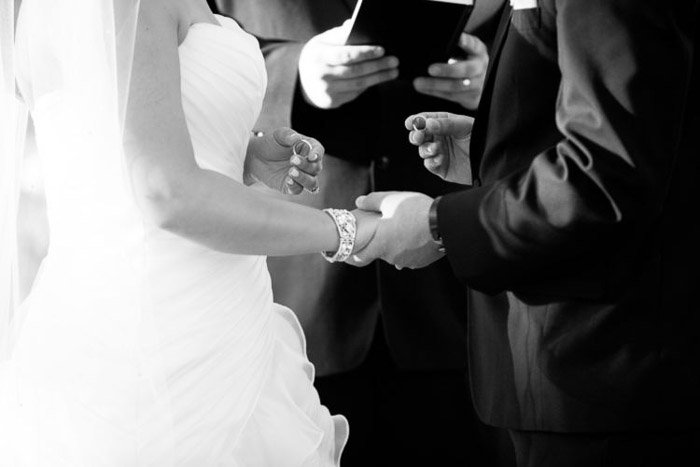 Black and white wedding photography close up of a bride and groom taking their vows.