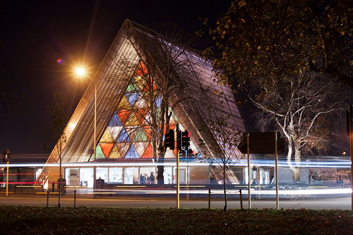 Front view of the brightly coloured Transitional Cathedral (aka 'Cardboard Cathedral'), New Zealand, at night. Architecture Photography.
