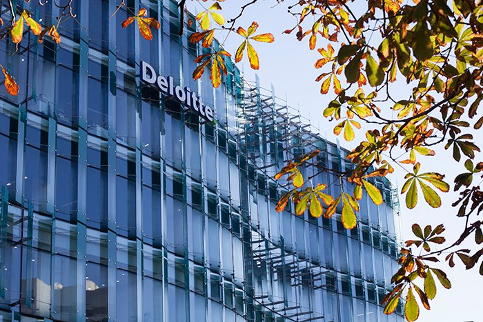 Facade of a multi windowed modern building with 'Deloitte' logo, leaves from a tree in the foreground. Architectural photography