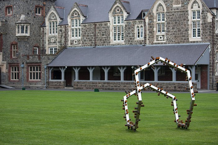 Photo of Anton Parsons artwork 'Acquiesce' on the grass outside a large stone building. Architecture Photography.