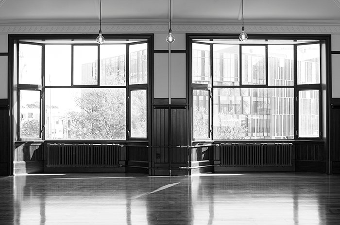 Black and white photograph of a large empty room with 2 big french windows, the restored former billiards room of the Midland Club Building, Christchurch, New Zealand.