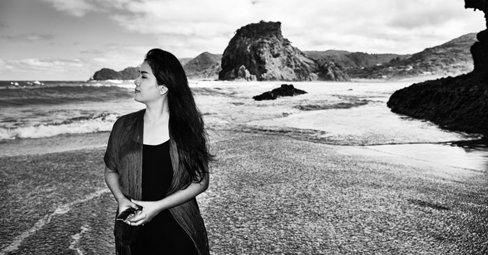 Black and white travel photo of a girl walking on Pina beach, New Zealand, rough waves and rocky coastline behind her