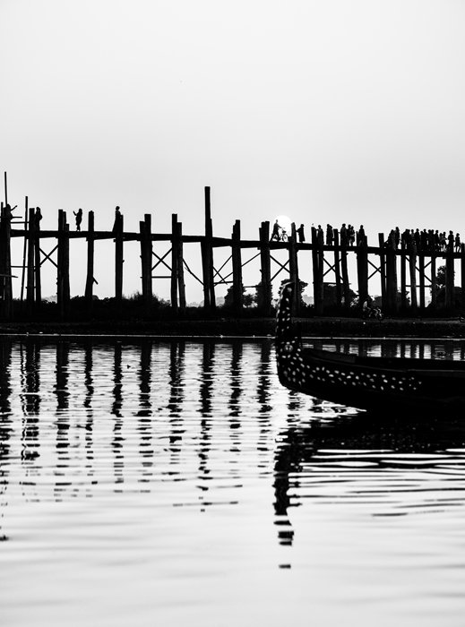 Black and white travel photo of the U-Bein bridge in Myanmar, the bridge and a boat nicely reflected in the water