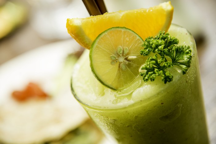 A close up of a green cocktail drink in colour