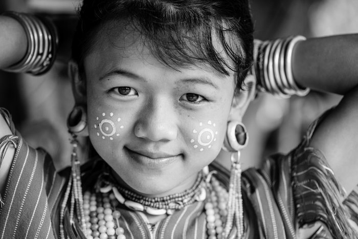 portrait of a young Kayaw girl putting her hair up