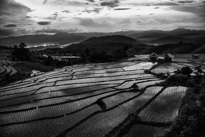 black and white overhead landscape photo of flooded paddie fields, the dark hills and cloudy sky are beautifully reflected in the water below.