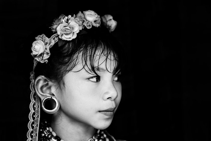 black and white travel portrait of a young girl with white flowers in her hair and traditional jewellery